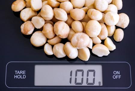 black gram: Macadamia nuts on digital scale displaying 100 gram.
