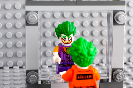 Tambov, Russian Federation - May 30, 2017 Lego The Joker in Arkham suit looks at himself in the mirror and sees himself in his favorite suit. Studio shot.