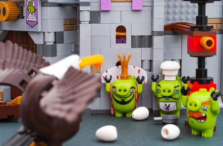 Tambov, Russian Federation - July 20, 2016 Lego Angry Birds. Three Bad Piggies surrender to Mighty Eagle near King Pigs Castle. Studio shot.