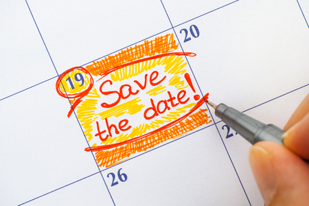 Woman fingers with red pen writting reminder Save the Date. Stock Photo