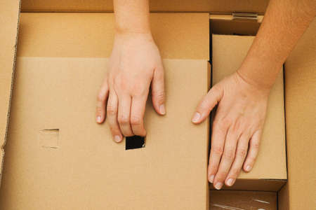 to unpack: Two woman hands unpacking big cardboard box. Close-up. Stock Photo