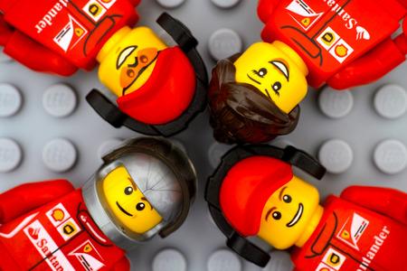 Tambov, Russische Federatie - 15 juni 2017 Vier Lego Ferrari-teambemanningsminifiguren op grijze basisplaatachtergrond. Studio opname.