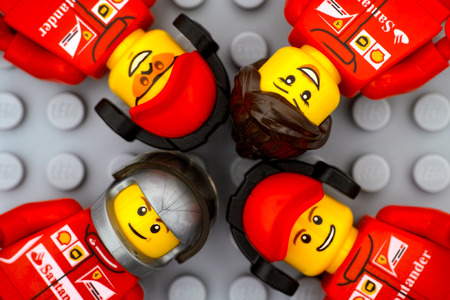 Tambov, Russian Federation - June 15, 2017 Four Lego Ferrari team crew members minifigures on gray baseplate background. Studio shot.