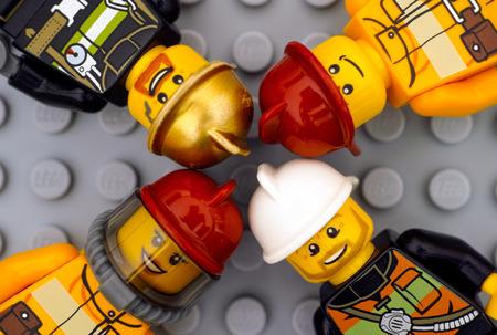 fireman: Tambov, Russian Federation - June 15, 2017 Four Lego firemans minifigures on gray baseplate background. Studio shot.