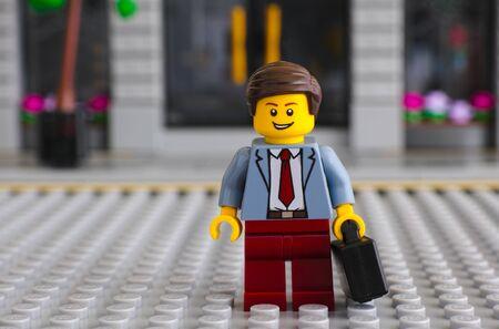 Tambov, Russische Federatie - 22 juni 2017 Lego zakenman met koffer blijven op Lego grijze grondplaat tegen bankgebouw. Studio opname. Redactioneel