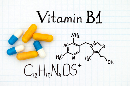 Chemical formula of Vitamin B1 and some pills. Stock Photo