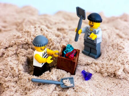 Tambov, Russian Federation - January 24, 2017 Two Lego robbers digging out box with gems from sand. Studio shot.