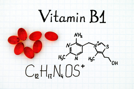 Chemical formula of Vitamin B1 and red pills. Stock Photo