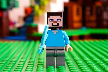 Tambov, Russian Federation - June 25, 2017 LEGO Minecraft. Steve minifigure with diamond sword. Green baseplate. Studio shot.