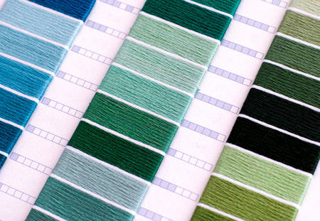 Samples of green and blue cotton thread. Close-up.