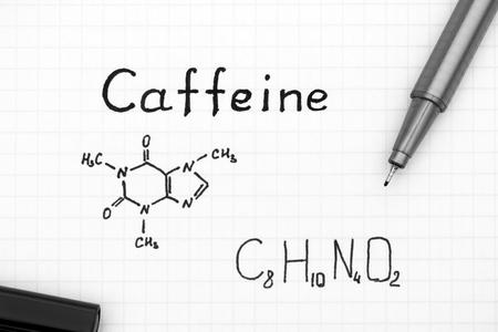 Chemical formula of Caffeine with black pen. Close-up.