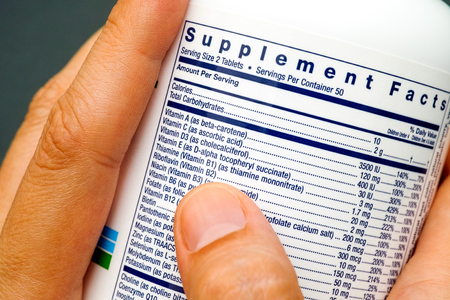 White plastic jar with supplement facts of multivitamins in woman hands.
