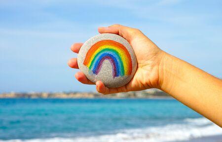 Mano de la mujer que sostiene el guijarro con el arco iris pintado contra el cielo azul y el mar. Foto de archivo - 85340707