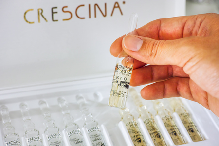 Paphos, Cyprus - November 13, 2015 Woman hand with ampoule of Crescina Re-Growth in front of Crescina treatment box. Shallow depth of field. Crescina HFSC preserves cell longevity, fights against ageing and promotes the physiological hair growth. Made by  Editorial
