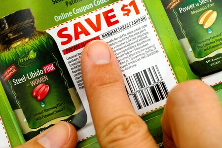 miserly: Tambov, Russian Federation - June 18, 2017 Woman fingers on Irwin Naturals discount coupon.