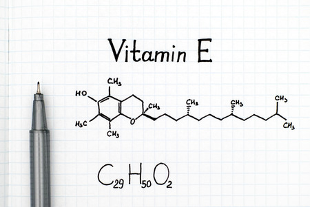 Chemical formula of Vitamin E with black pen. Close-up.