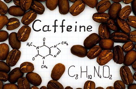 Chemical formula of Caffeine with coffee beans background. Close-up.