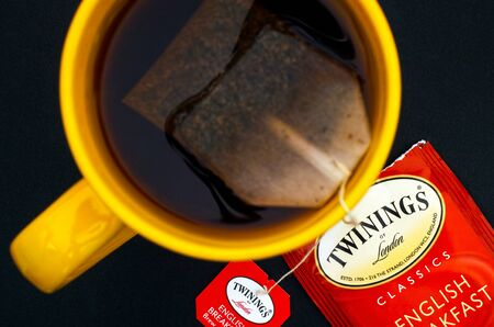 Tambov, Russian Federation - August 28, 2017 Cup of Twinings English Breakfast tea with teabag on black background. Top view. Studio shot.