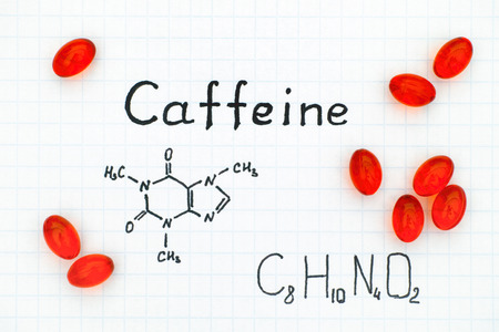 Chemical formula of Caffeine with red pills. Close-up.