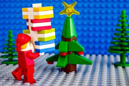 Tambov, Russian Federation - November 06, 2017 Lego Santa Claus with stack of presents near christmas tree. Studio shot.