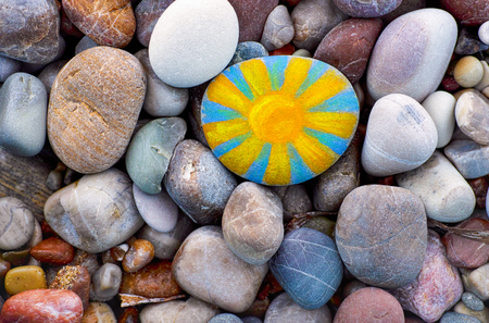 Bright sun painted on pebble. Pebbles background.