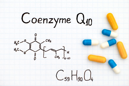Chemical formula of Coenzyme Q10 with some pills. Close-up. Фото со стока