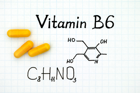Chemical formula of Vitamin B6 with yellow pills. Close-up.