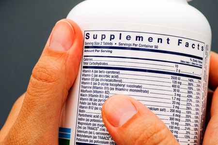 White plastic jar with supplement facts of multivitamins in person hands. Close-up.