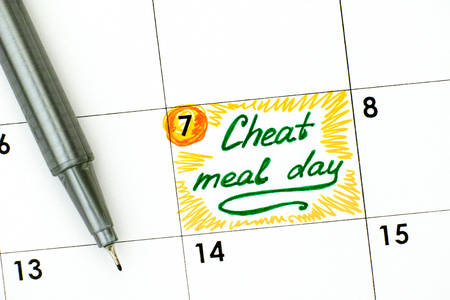 Reminder Cheat Meal Day in calendar with green pen. Close-up.