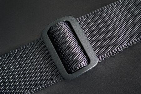 Buckle on black belt. Black background.