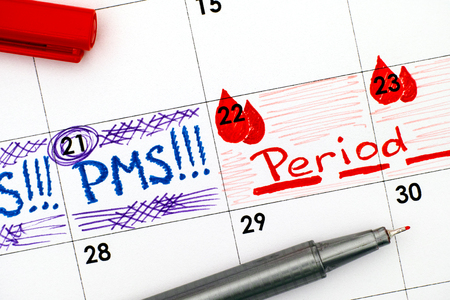 Reminder PMS and Period in calendar with red pen. Close-up.