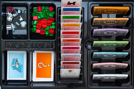 Tambov, Russian Federation - January 26, 2018 Monopoly Board Game box with Tokens, Title Deed Cards, Chance Cards, Community Chest Cards, Houses, Hotels, Dices, Money Pack.