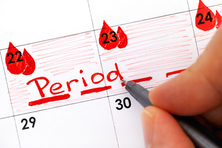 Woman fingers with pen writing reminder Period in calendar. Close-up.