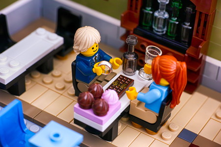 Tambov, Russian Federation - January 04, 2018 Lego couple sitting at the table in Restaurant. Man gets ready to propose with the ring. Studio shot.