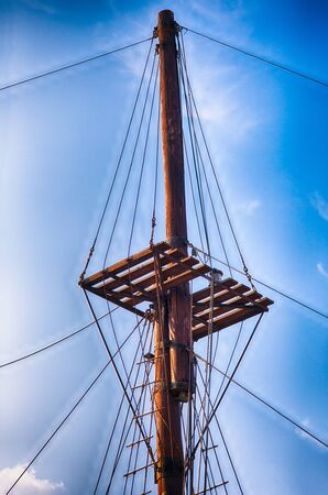 Wooden ship mast against blue sky.