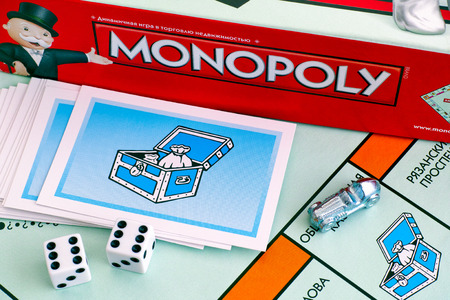 Tambov, Russian Federation - January 26, 2018 Monopoly Board Game box, Community Chest Cards, tokens, dices on gameboard. Studio shot.
