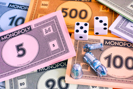 Tambov, Russian Federation - January 26, 2018 Monopoly money packs with tokens and dice. Studio shot.