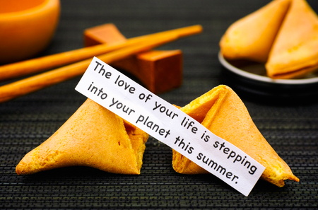 Paper strip with phrase The Love of Your Life is Stepping into Your Planet This Summer from fortune cookie, another cookie and chopsticks on black napkin background.