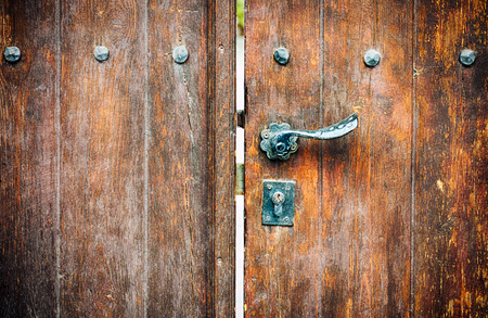 Wooden gate with door knob and keyhole. Close-up. Stock Photo