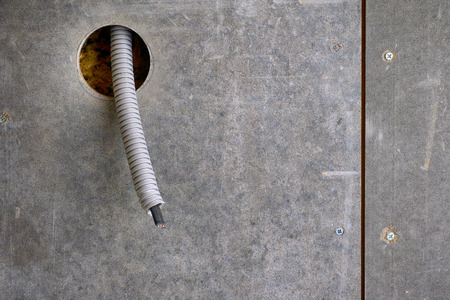 Plastic corrugated pipe with electric cable inside sticking out of wall for power socket. Stok Fotoğraf