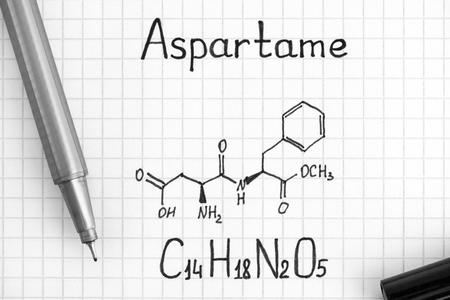 Chemical formula of Aspartame with black pen. Close-up.