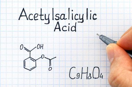 Person hand with pen writing chemical formula of Acetylsalicylic Acid. Close-up.