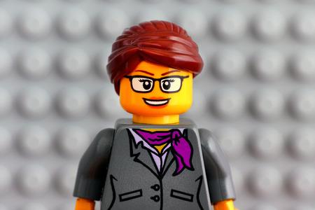 Tambov, Russian Federation - July 29, 2018 Portrait of Lego businesswoman minifigure with gray baseplate background. Studio shot.