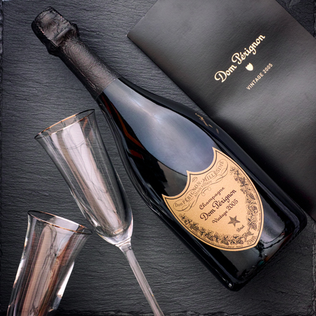 Tambov, Russian Federation - August 16, 2018 Bottle of Champagne Dom Perignon Vintage 2005 with two wineglasses and booklet on black stone background. Studio shot.