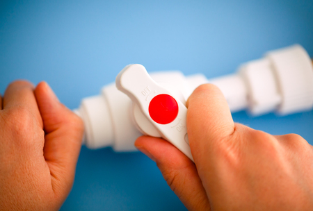 Person hands turning the switch on pipe. Close-up. Stock Photo