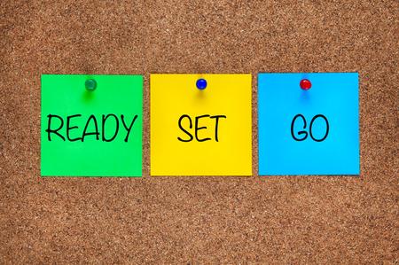 Tres notas de papel en el tablero de corcho con las palabras Ready, Set, Go. Foto de archivo