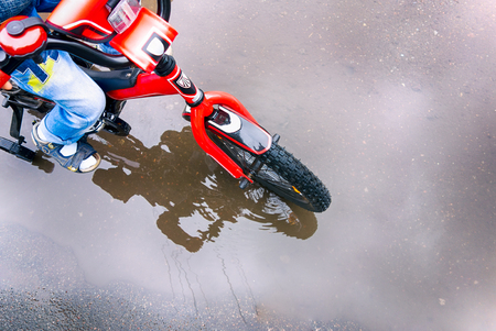 Child riding on bicycle through the puddle. Close-up.