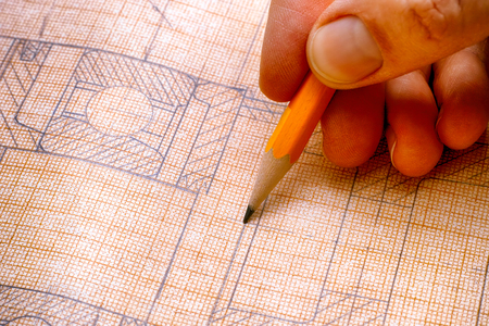 Person hand with pencil and technical drawing. Close-up.