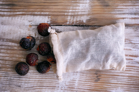 Soap nuts spilling from wash bag on wooden background. Top view. Stock Photo