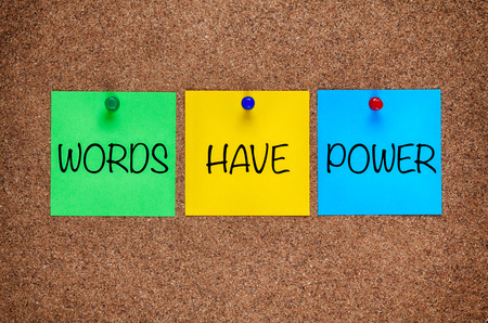Three blanks post notes with phrase Words Have Power on corkboard. Foto de archivo - 114410792